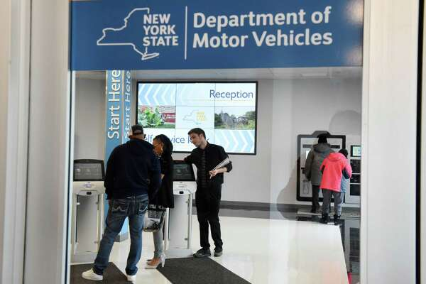 Nickie Valdez, center, and Zachary Coonradt, right, assist customers as they enter the new Albany Department of Motor Vehicles office on Tuesday, March 19, 2019, at 855 Central Avenue in Albany, N.Y. The center was relocated from the South End. (Will Waldron/Times Union)