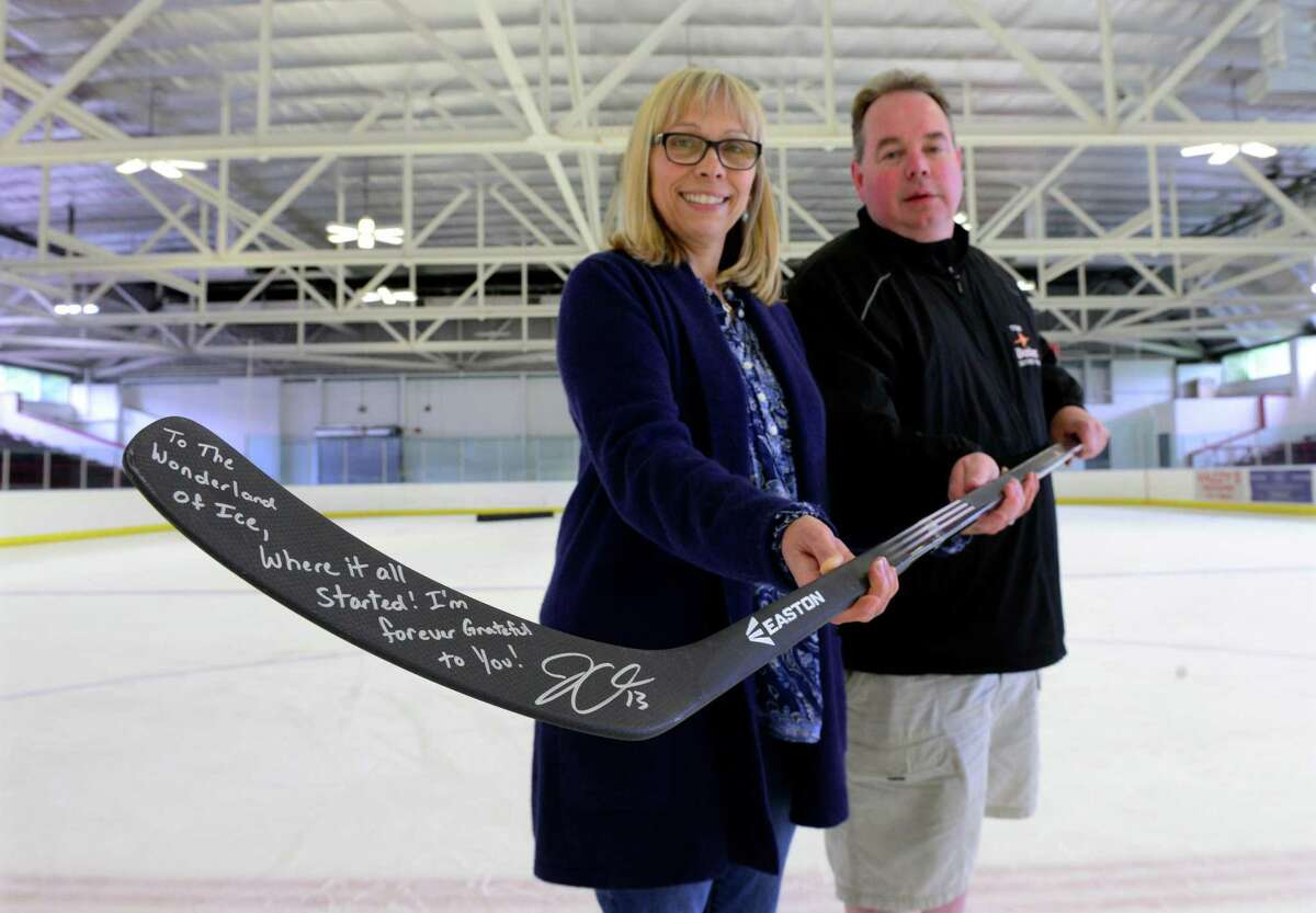 Wonderland of Ice General Manager Lisa Fedick and Hockey Director John Ferguson hold a hockey stick signed by Olympian Julie Chu at the rink in Bridgeport, Conn., on Thursday June 18, 2015. Fedick was Chu's first figure skating coach and helped her make the transition to hockey. Chu will be running a hockey camp at Wonderland of Ice from July 28 to 31.