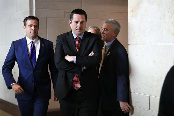 Rep. John Ratcliffe R-Texas, left, and House Intelligence Committee Ranking Member Devin Nunes, R-Calif., center, leave a closed-door meeting of the House Intelligence Committee with testimony from Michael Cohen, President Donald Trump's former personal lawyer, Monday, Feb. 5, 2018, to attend a vote on Capitol Hill in Washington. (AP Photo/Jacquelyn Martin)