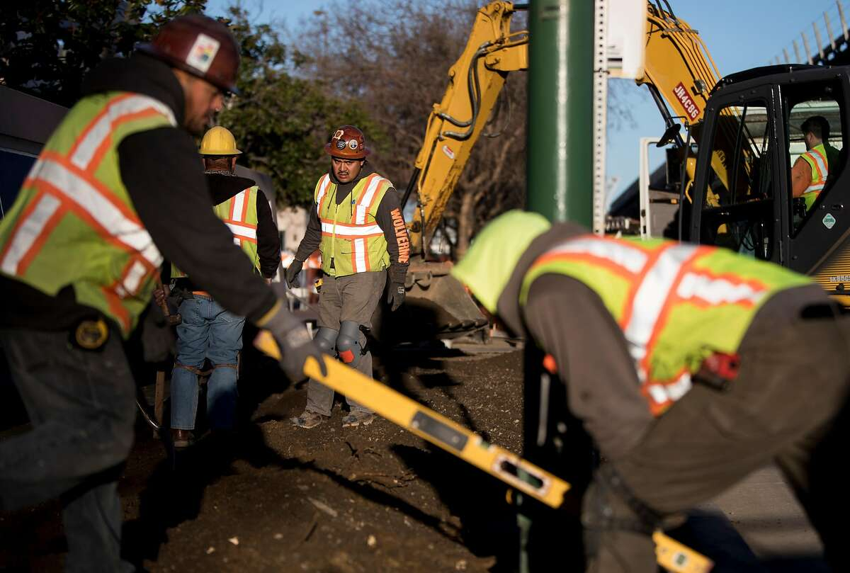 Construction crews work on a streetscape project in front of the U.S. Post Office along 7th Street near Wood Street in Oakland, Calif. Thursday, March 14, 2019.