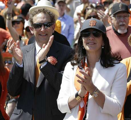 FILE - In this April 8, 2014, file photo, San Francisco Giants president and CEO Larry Baer, and his wife Pam, applaud before an opening day baseball game against the Arizona Diamondbacks, in San Francisco. Baer is taking a leave of absence from the team following the release of a video showing him in a physical altercation with his wife. The Giants board of directors released a statement Monday, March 4, 2019, saying that Baer has been granted a request to take personal time away from the team. (AP Photo/Eric Risberg, File)