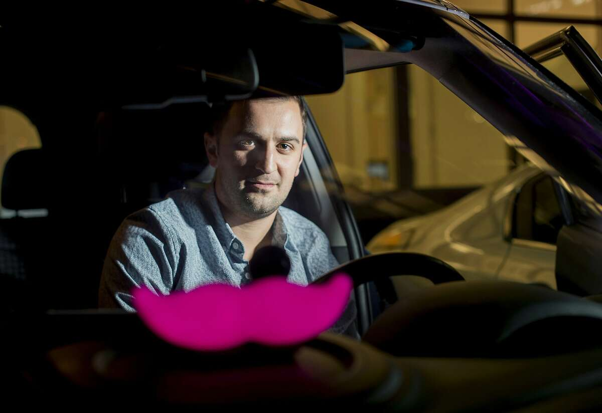 """FILE - In this Jan. 26, 2015, file photo, Lyft co-founder John Zimmer displays his company's """"glowstache"""" following a launch event in San Francisco. Ride-hailing giant Lyft is releasing financial details about the company in a federal filing before it begins selling its stock to the public. (AP Photo/Noah Berger, File)"""