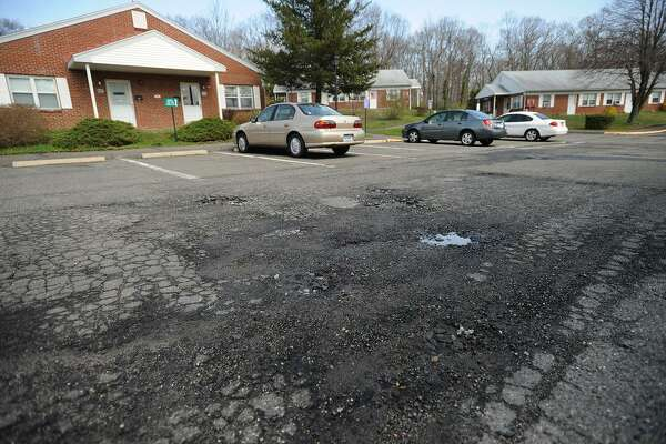 Potholes on Hedgehog Circle in the Stern Village housing complex in Trumbull, Conn. on Thursday, May 1, 2014. The complex, run by the Trumbull Housing Authority, is for the elderly and disabled.