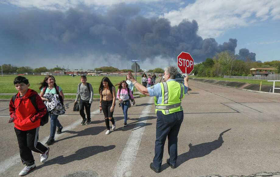 Deer Park PD Crossing Guard Adell Boren makes sure Deer Park Jr. High School students are safe as they cross East 13th and Meadowlark Streets in spite of a chemical fire burning nearby Tuesday, March 19, 2019, in Deer Park. Photo: Steve Gonzales, Staff Photographer / © 2019 Houston Chronicle