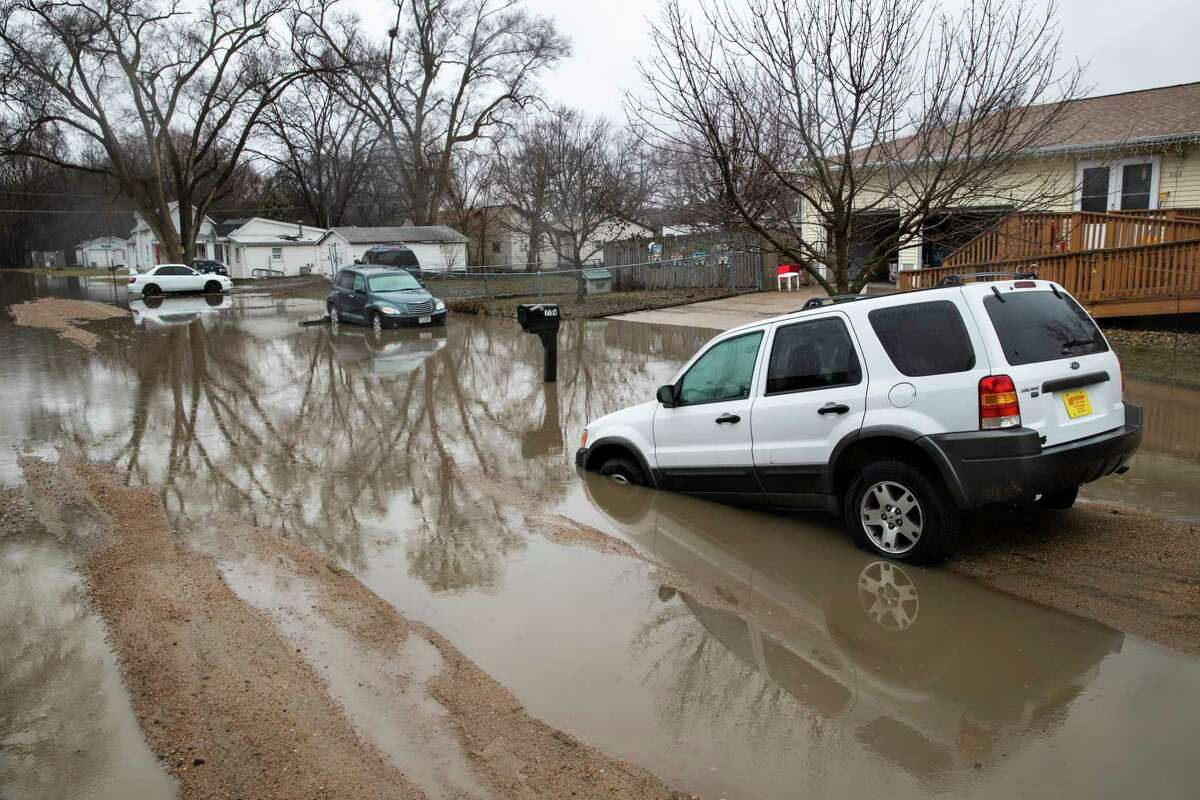 Cars are stuck in floodwaters Tuesday, March 19, 2019, in Fremont, Neb. Flooding is expected throughout the week in several states as high water levels flow down the Missouri River. Swollen rivers have already breached more than a dozen levees in Nebraska, Iowa and Missouri, according to the U.S. Army Corps of Engineers. (Brendan Sullivan/Omaha World-Herald via AP)