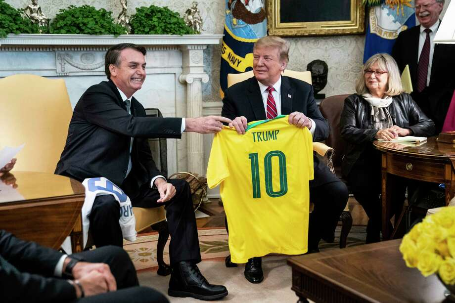 President Trump and Brazil's Presidentl Jair Bolsonaro trade soccer jerseys in the Oval Office at the White House on Tuesday. Photo: Washington Post Photo By Jabin Botsford / The Washington Post