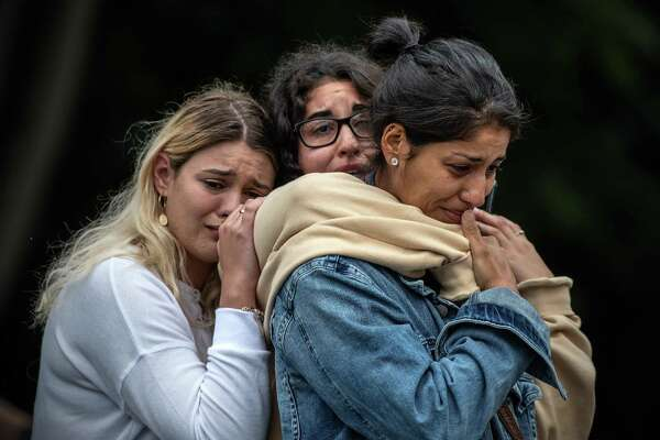 "Women weep during a vigil in Christchurch, New Zealand, for those killed in the mosque attacks. Here's what alleged gunman wrote: ""Were/are you a supporter of Donald Trump? As a symbol of renewed white identity and common purpose? Sure."""