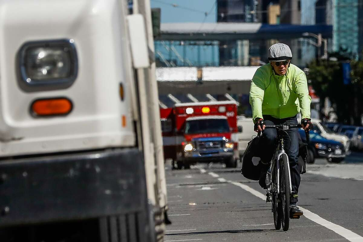 A biker rides on Howard Street where a cyclist was killed last Friday after being struck by a vehicle in San Francisco, California, on Monday, March 11, 2019