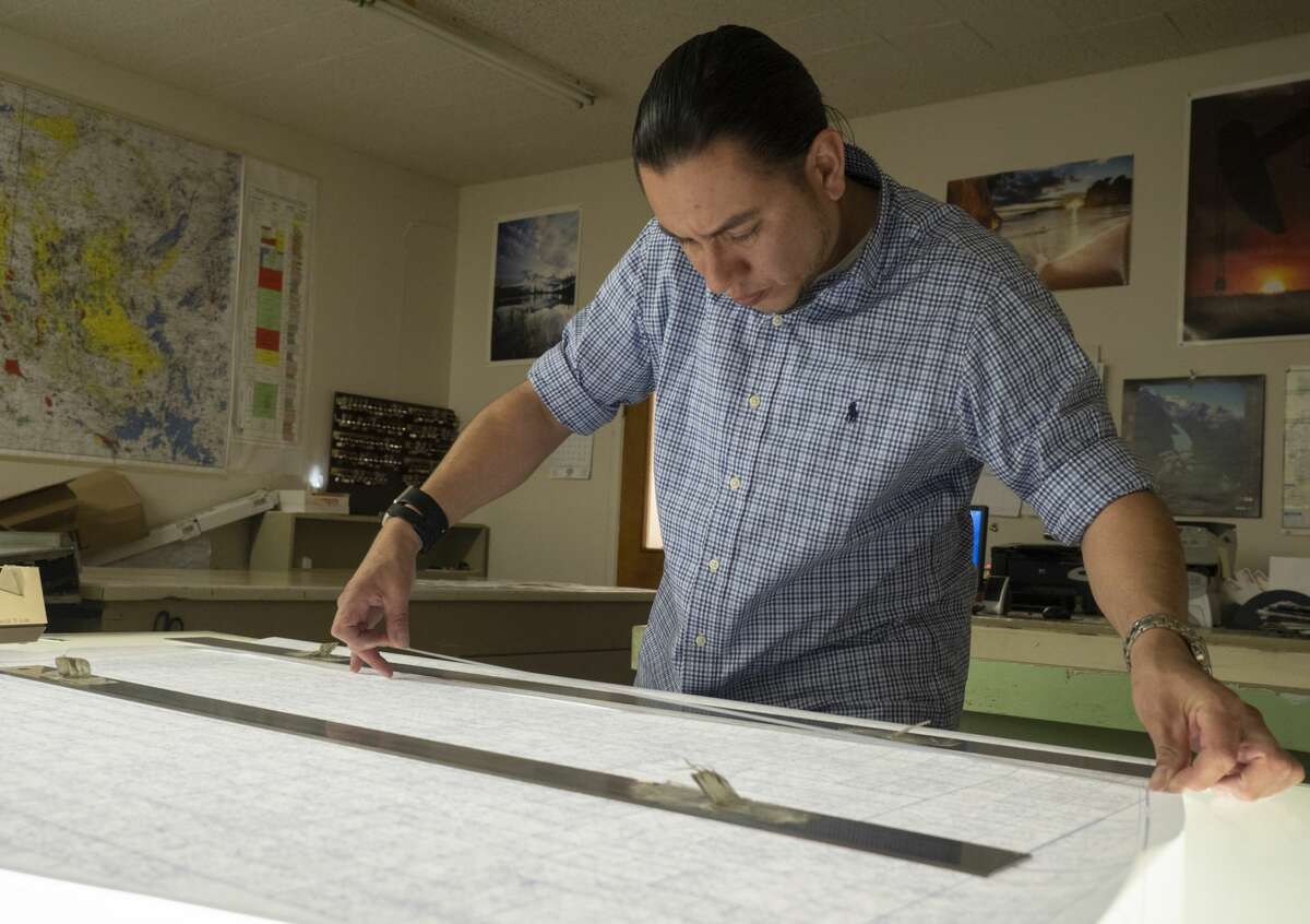 Josue Guerrero works on lining up two printouts to make one full size map 03/19/2019 at Midland Map Company, who is being bought by Drillinginfo. Tim Fischer/Reporter-Telegram