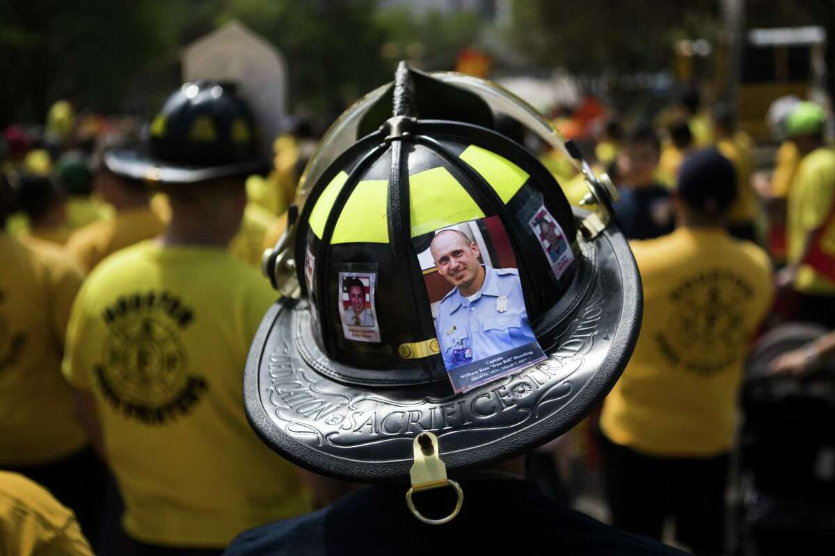 A Houston firefighter wears a helmet on Tuesday, March 19, 2019, in Houston with the photo of Captain William Ross