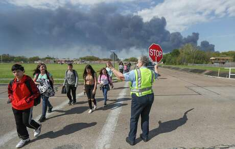 Deer Park PD Crossing Guard Adell Boren makes sure Deer Park Jr. High School students are safe as they cross East 13th and Meadowlark Streets in spite of a chemical fire burning nearby Tuesday, March 19, 2019, in Deer Park.