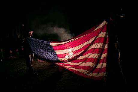 Boy Scouts leadership open an American flag to explain the young scouts how will a retired flag will eventually be disposed during a ceremony by a fire at a camporee on Saturday, March 2, 2019, in Chappell Hill.
