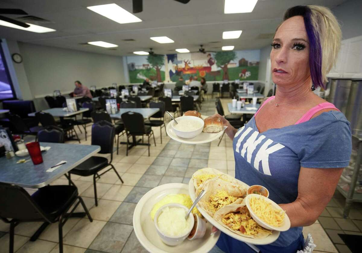 Charlie Dunn serves food at Ken's Restaurant, 1122 Center St., where she said the lunch business was slow Tuesday, March 19, 2019, in Deer Park. A chemical fire nearby at Intercontinental Terminals Company which began Sunday morning, continues to send dark smoke over Deer Park.