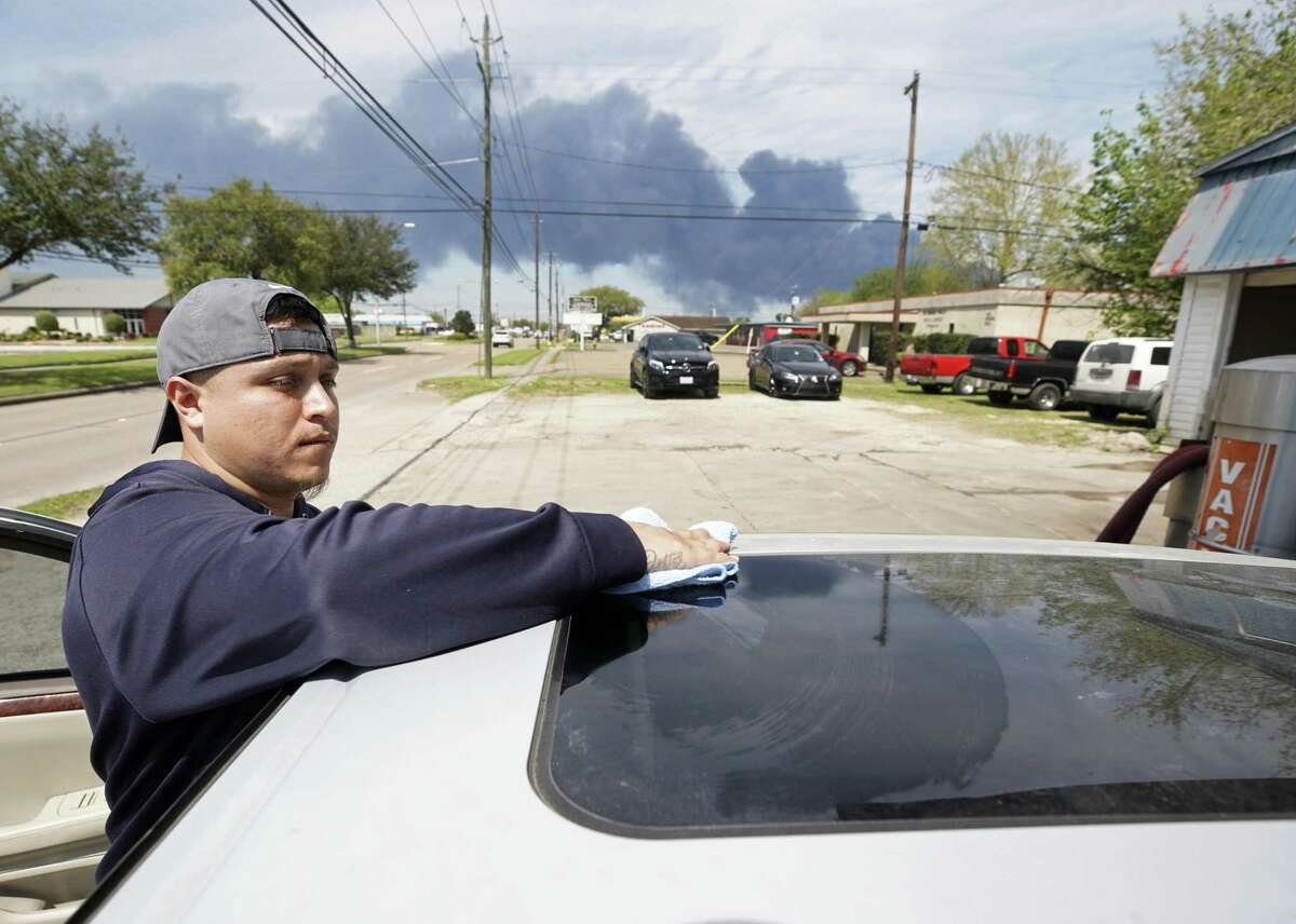 Carlos Razo cleans a car at Juan's Hand Carwash, 1905 Center St., as the chemical fire at Intercontinental Terminals Company continues to send dark smoke over Deer Park Tuesday, March 19, 2019. The fire began Sunday morning.