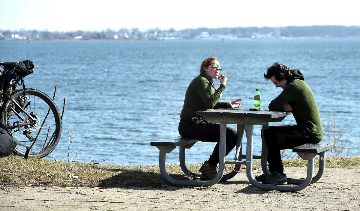 Emily Wasem (left) and Dylan Packard take a break at Long Wharf Park in New Haven while on the first leg of their bicycle trip from Cheshire to Princeton Junction, New Jersey, on March 11, 2019. Wasem is from Princeton Junction, New Jersey, and Packard is from Kensington, New Hampshire.