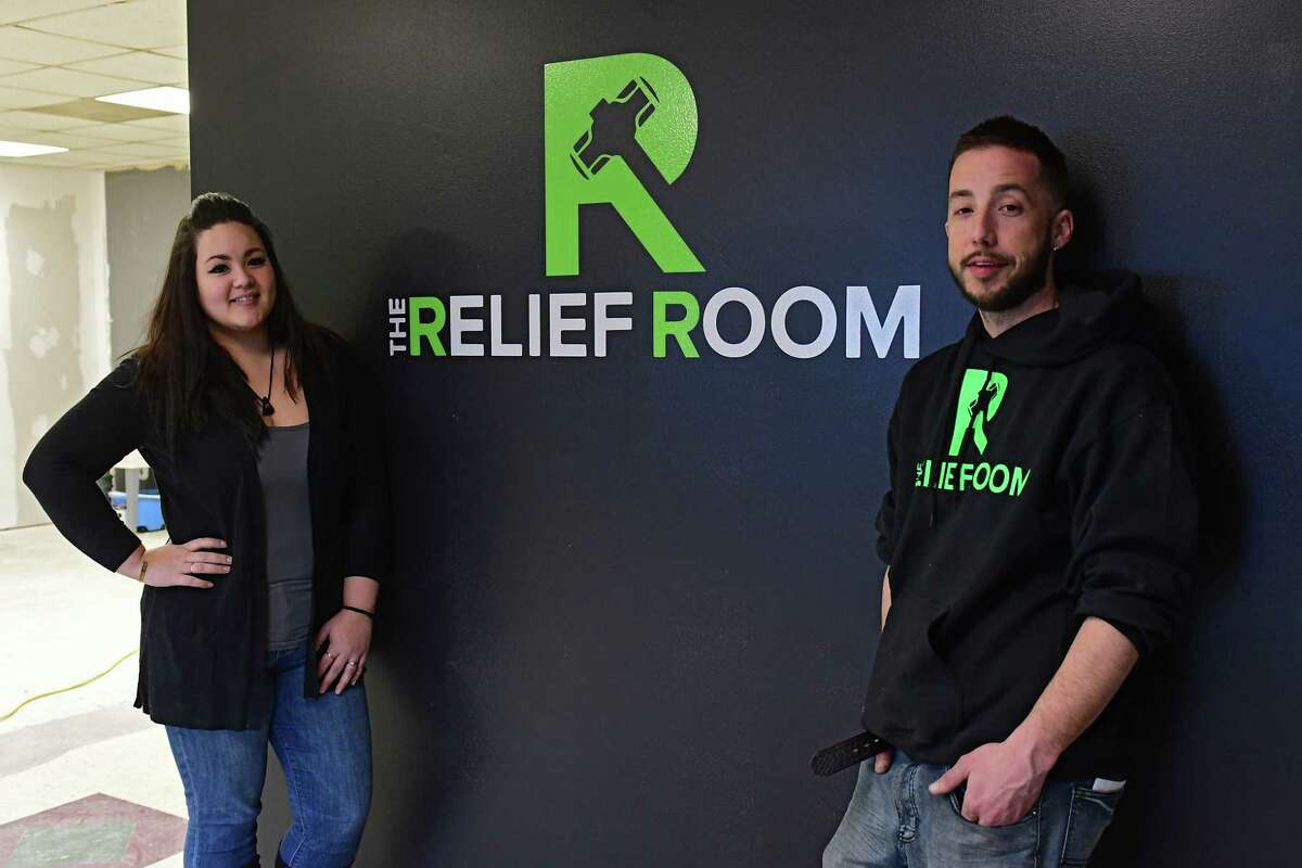 """Lisa and her co-partner/fiance Steve Cusano stand by their logo in The Relief Room on Tuesday, March 19, 2019 in Malta, N.Y. The business is a so-called """"rage room,"""" where people pay so they can don protective gear and smash up office and household items to relieve their stress. It is the first of its kind in the area. (Lori Van Buren/Times Union)"""