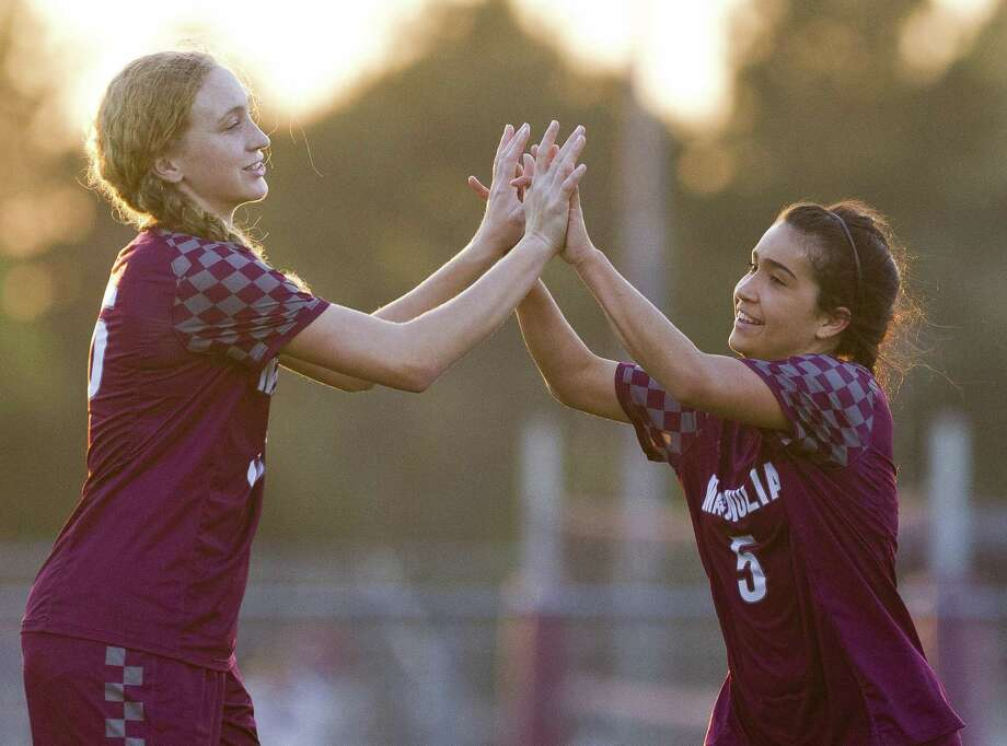 Magnolia forward Izzy Cardenas (5) gets a high-five from forward Erin Mooneyham (16) after Cardenas' second goal of the first period of a District 19-5A high school girls soccer match at Magnolia High School, Tuesday, March 19, 2019, in Magnolia. Photo: Jason Fochtman, Houston Chronicle / Staff Photographer / © 2019 Houston Chronicle