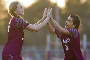 Magnolia forward Izzy Cardenas (5) gets a high-five from forward Erin Mooneyham (16) after Cardenas' second goal of the first period of a District 19-5A high school girls soccer match at Magnolia High School, Tuesday, March 19, 2019, in Magnolia.
