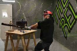 "Co-owner Steve Cusano uses a bat to smash an empty liquor bottle in The Relief Room on Tuesday, March 19, 2019 in Malta, N.Y. The business is a so-called ""rage room,"" where people pay so they can don protective gear and smash up office and household items to relieve their stress. It is the first of its kind in the area. (Lori Van Buren/Times Union)"