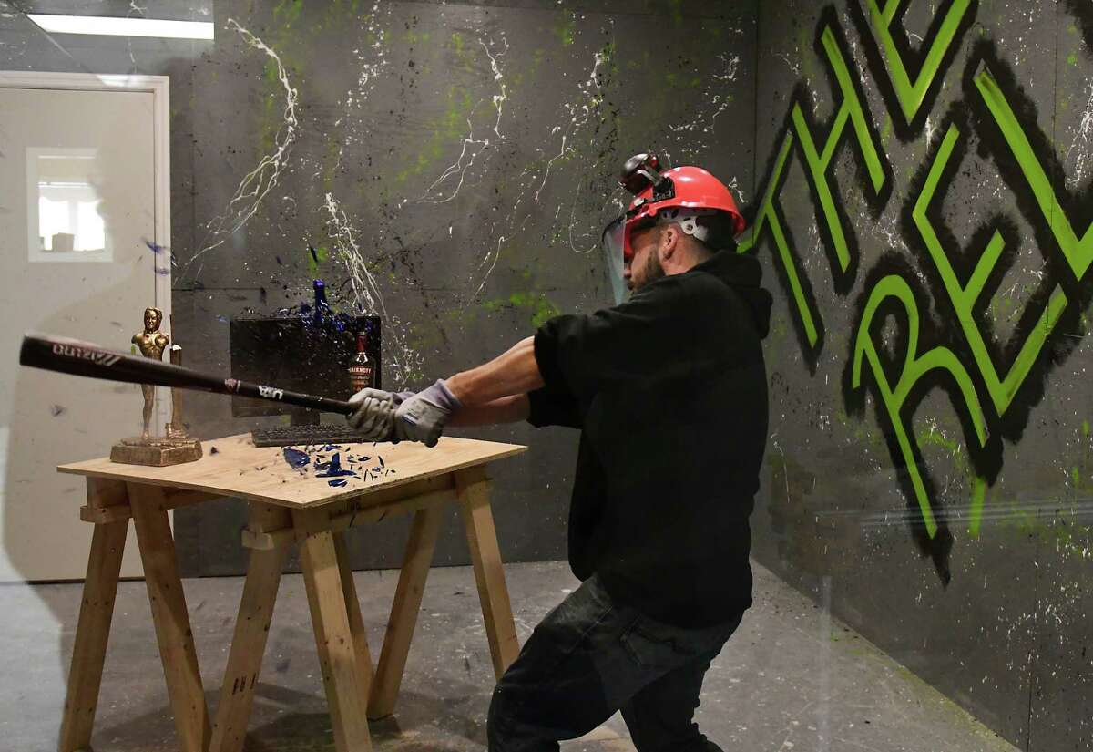 """Co-owner Steve Cusano uses a bat to smash an empty liquor bottle in The Relief Room on Tuesday, March 19, 2019 in Malta, N.Y. The business is a so-called """"rage room,"""" where people pay so they can don protective gear and smash up office and household items to relieve their stress. It is the first of its kind in the area. (Lori Van Buren/Times Union)"""