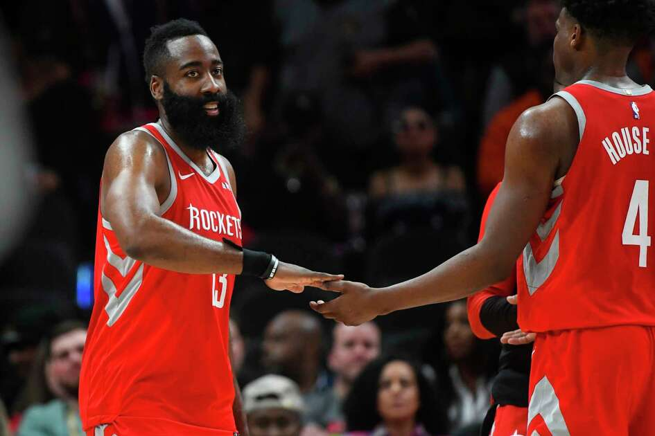 Houston Rockets guard James Harden (13) gives props to forward Danuel House Jr. during a time-out in the second half of an NBA basketball game Tuesday, March 19, 2019, in Atlanta. (AP Photo/John Amis)