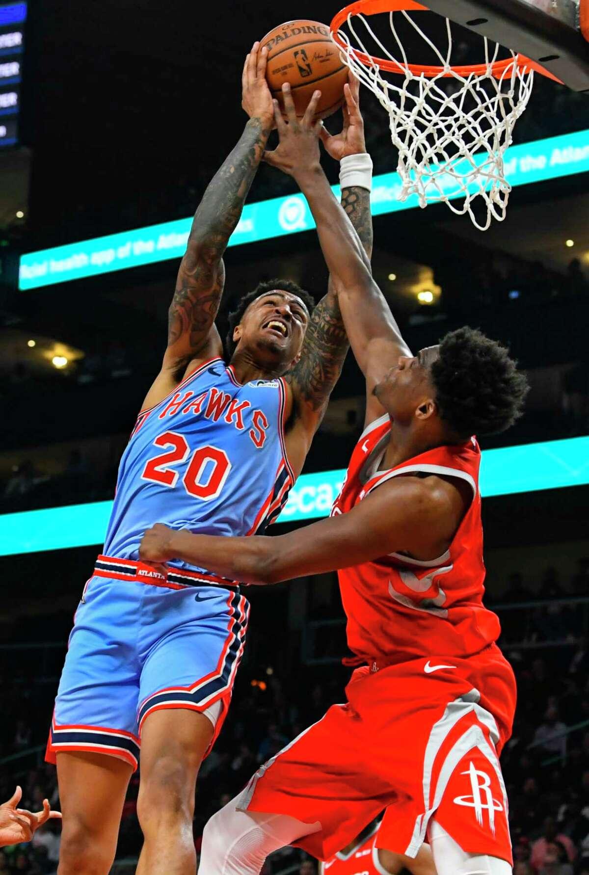 Atlanta Hawks forward John Collins (20) is fouled shooting by Houston Rockets forward Danuel House Jr. during the second quarter of an NBA basketball game Tuesday, March 19, in Atlanta. (AP Photo/John Amis)