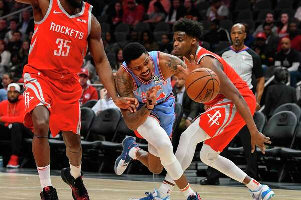 Atlanta Hawks guard Kent Bazemore splits the defense of Houston Rockets Kenneth Faried (35) and forward Danuel House Jr., right, during the first quarter of an NBA basketball game Tuesday, March 19, in Atlanta. (AP Photo/John Amis)