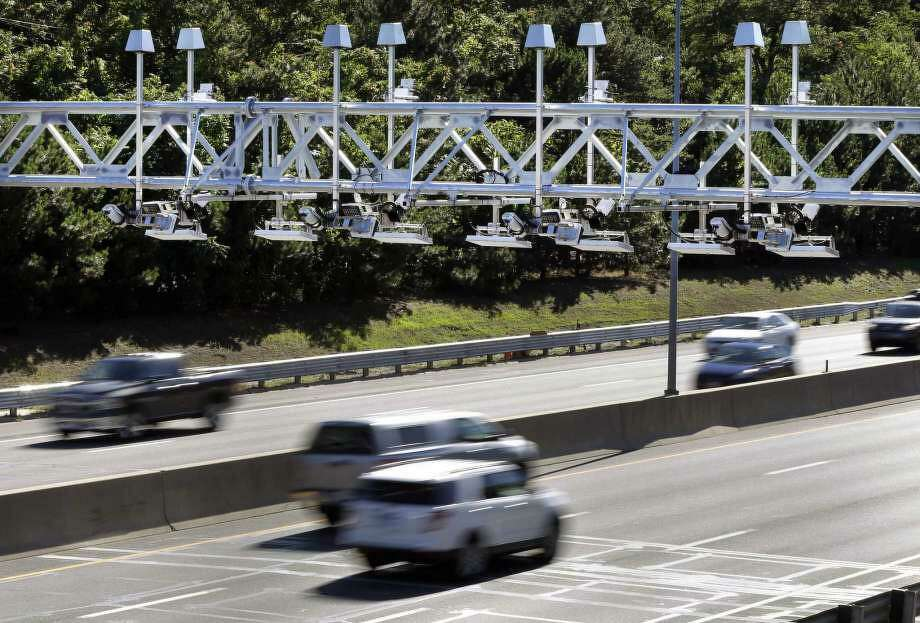 Cars pass under toll sensor gantries hanging over the Massachusetts Turnpike in Newton, Mass. Photo: Elise Amendola /AP