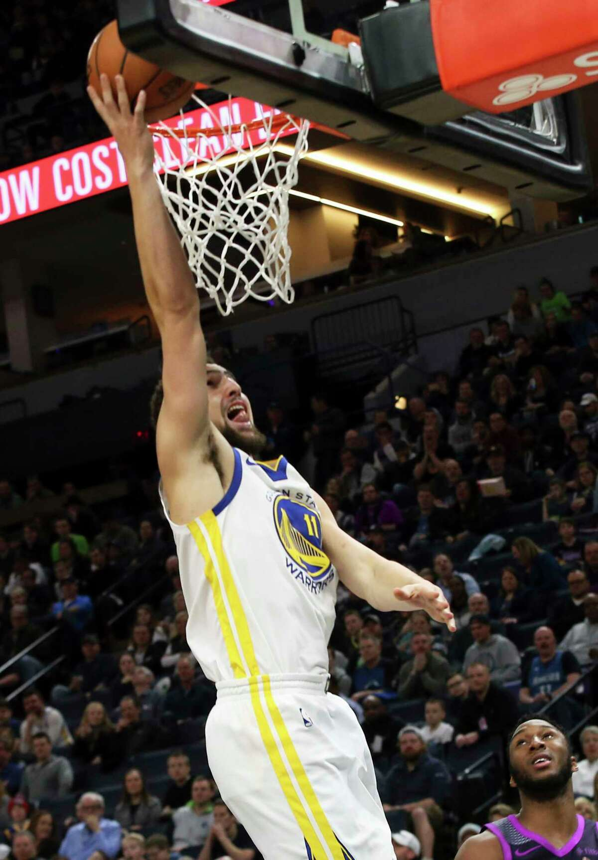 Golden State Warriors' Klay Thompson, left, lays up as Minnesota Timberwolves' Josh Okogie, lower right, watches in the second half of an NBA basketball game Tuesday, March 19, 2019, in Minneapolis. The Warriors won 117-107. Thompson scored 28 points. (AP Photo/Jim Mone)