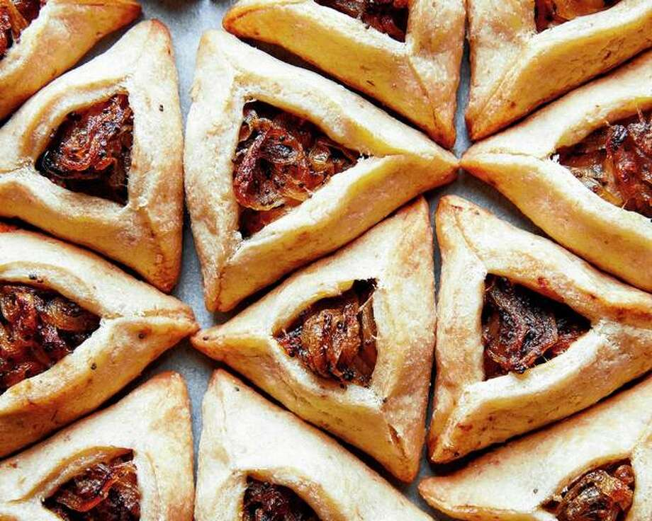 Hamantaschen, as essential to Purim as matzo is to Passover, typically are sweet, but the triangular cookies also can be served in this savory spinoff featuring caramelized onions and poppy seeds. Photo: Linda Xiao | The New York Times