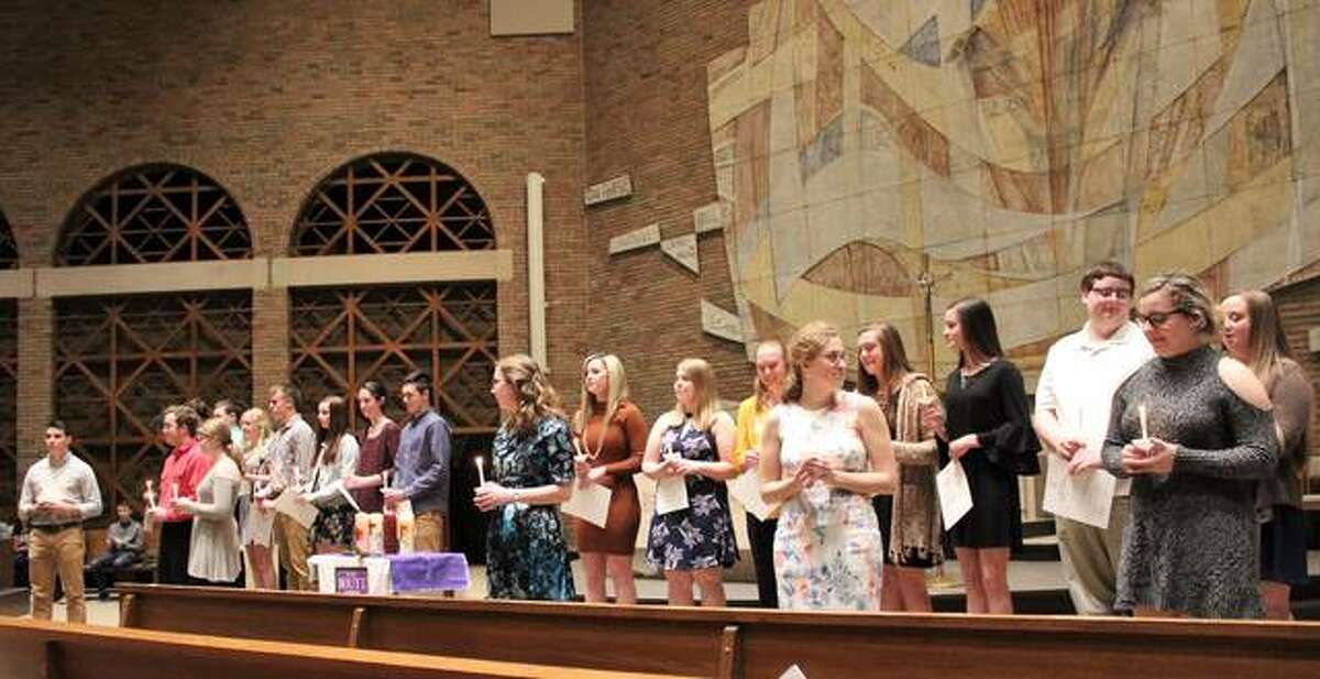 National Honor Society members hold candles during the Routt Catholic High School ceremony March 11.