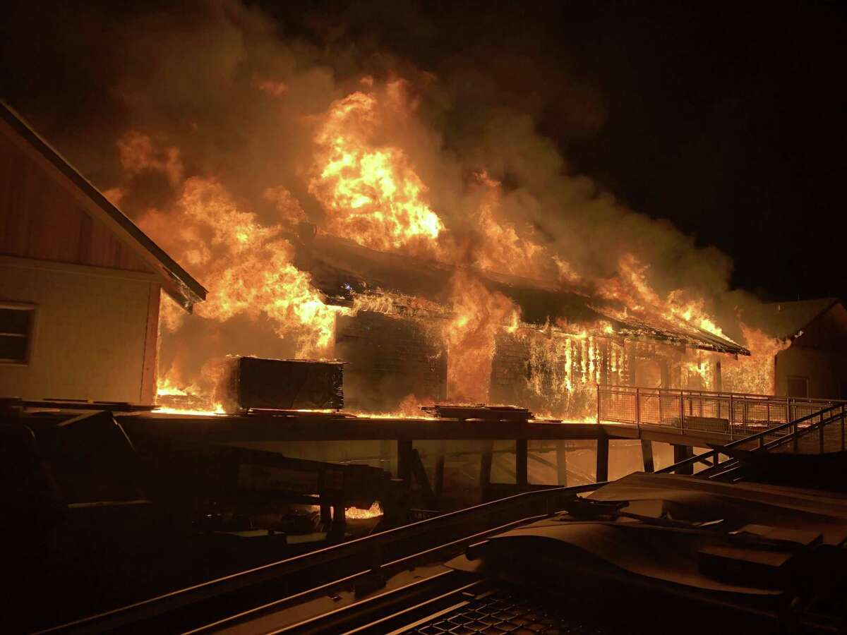 Fire engulfs a building under construction at Silver Sands State Part on Tuesday, March 19, 2019.