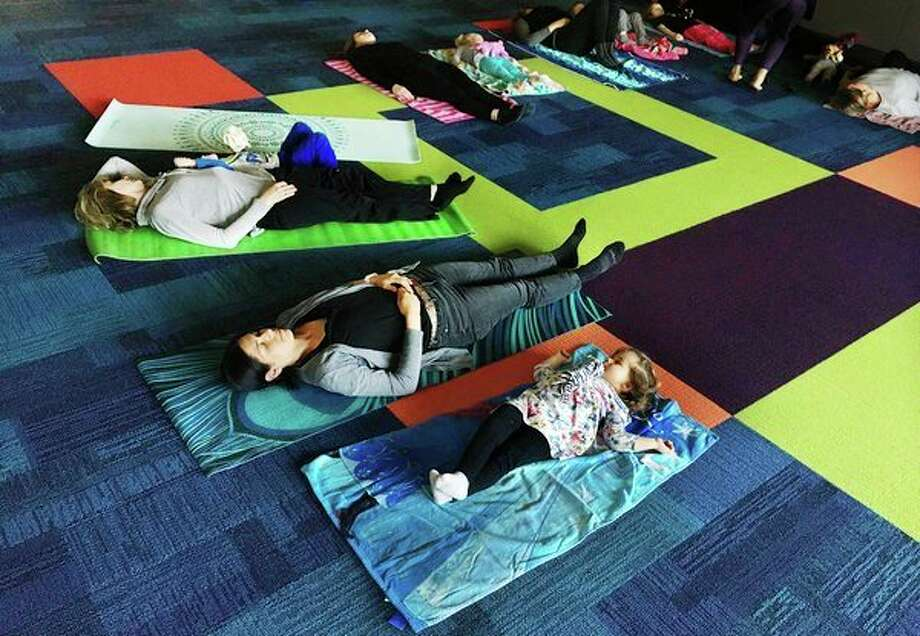 Midland residents Ellie Palmiter, 2, center right, and Kylie Palmiter, center left, lie back and focus on their breathing in the final minutes of a 'Storytime Yoga for Two' class hosted by Well-Bean Kids Yoga on Tuesday morning at the Grace A. Dow Memorial Library. For more photos, go to www.ourmidland.com. (Katy Kildee/kkildee@mdn.net)