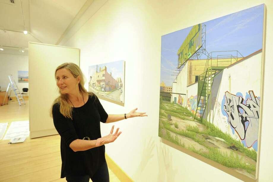 Curator Isabelle Schiavi chats about a piece by Artist Valeri Larko. Photo: Matthew Brown / Hearst Connecticut Media / Stamford Advocate