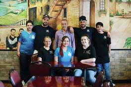 Sitting front left to right, Stacey Ausley, Angela Ordonez, and Allie Urista. Standing rear left to right, Sabian Memedi, Ozzy Memedi, Steve Memedi, Alex Memedi and Aelind Memedi pose for a photo at Mama Mia's Pizza.