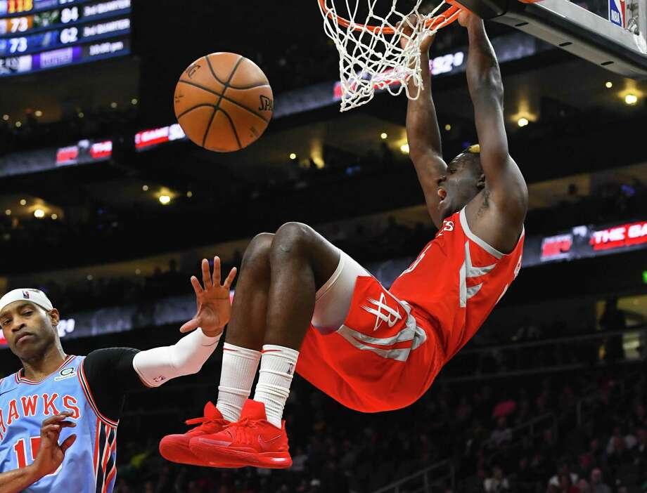 Houston Rockets center Clint Capela dunks in front of Atlanta Hawks forward Vince Carter, left, during the second half of an NBA basketball game Tuesday, March 19, in Atlanta. Houston won 121-105. (AP Photo/John Amis) Photo: John Amis, FRE / Associated Press / Copyright 2019 The Associated Press. All rights reserved