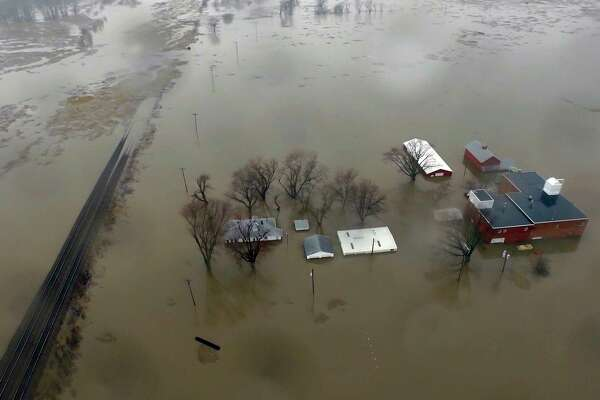 This Tuesday, March 19, 2019 aerial photo shows flooding along the Missouri River in Pacific Junction, Iowa. The U.S. Army Corps of Engineers says rivers breached at least a dozen levees in Nebraska, Iowa and Missouri. Hundreds of homes are damaged, and tens of thousands of acres are inundated with water. (DroneBase via AP)