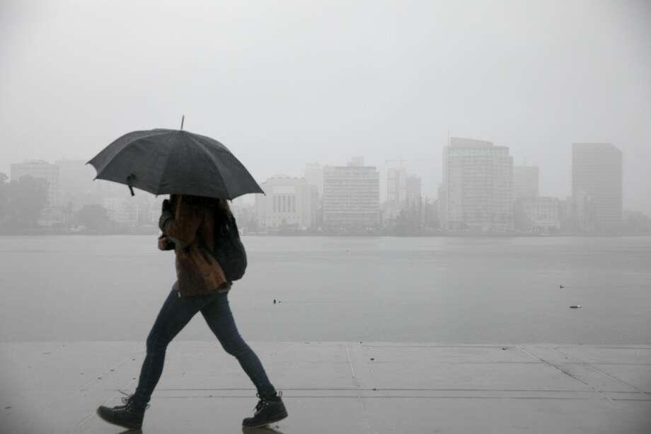 A pedestrian uses an umbrella for cover during a steady rainfall near Lake Merritt in Oakland, California on March 20, 2019. Photo: Douglas Zimmerman / SFGate