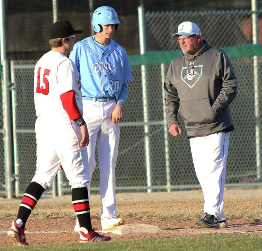 Jersey's Tucker Shalley (middle) gets instructions from first base coach Chris Skinner while Alton first baseman Adam Stilts walks to the bag during Monday's game at Alton High in Godfrey. Shalley drove in two runs Tuesday in a win over Southwestern at Ken Schell Field in Jerseyville. Photo: Greg Shashack / The Telegraph