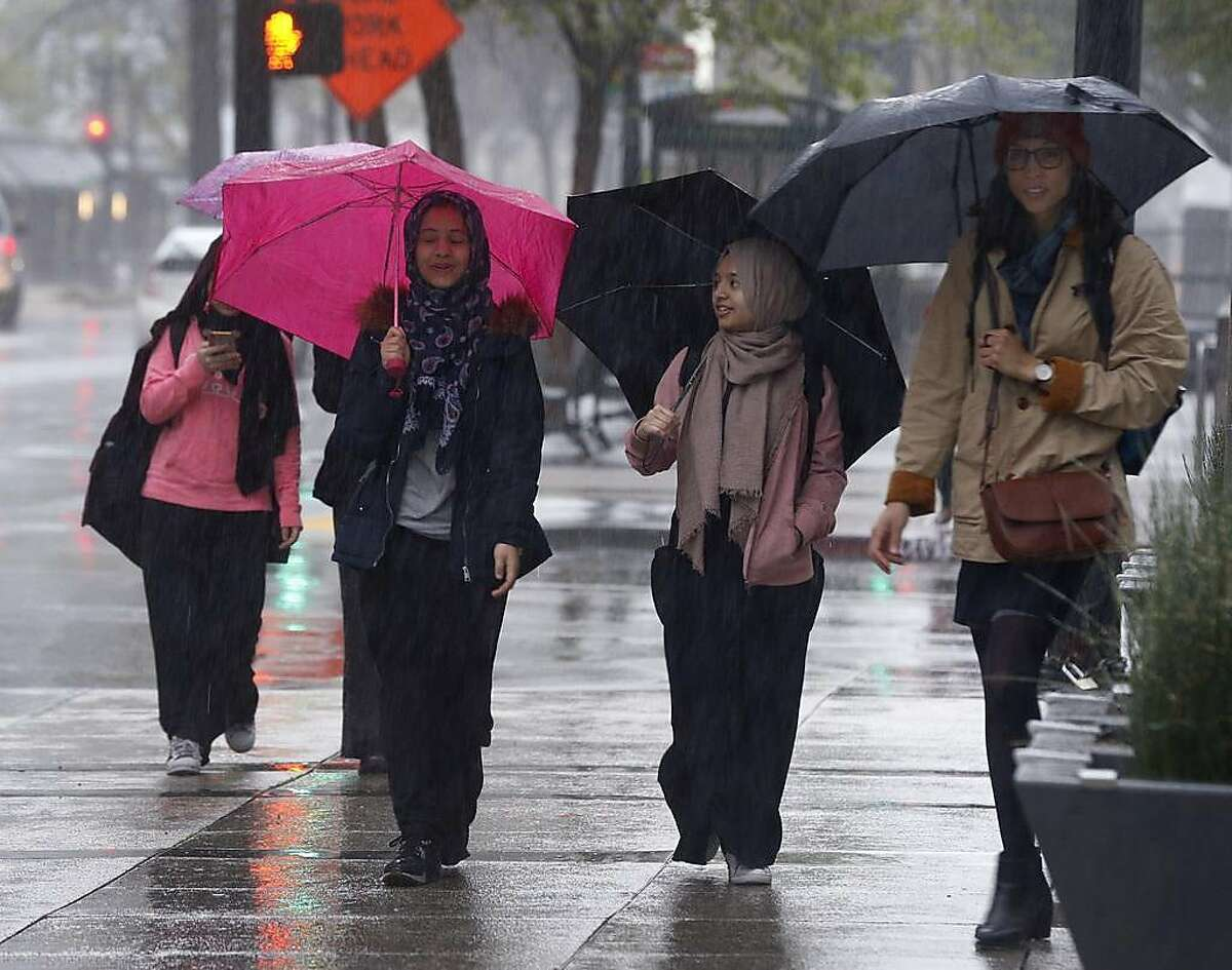 Pedestrians carry umbrellas on Broadway as another rainstorm drenches the region in Oakland, Calif. on Wednesday, March 20, 2019.