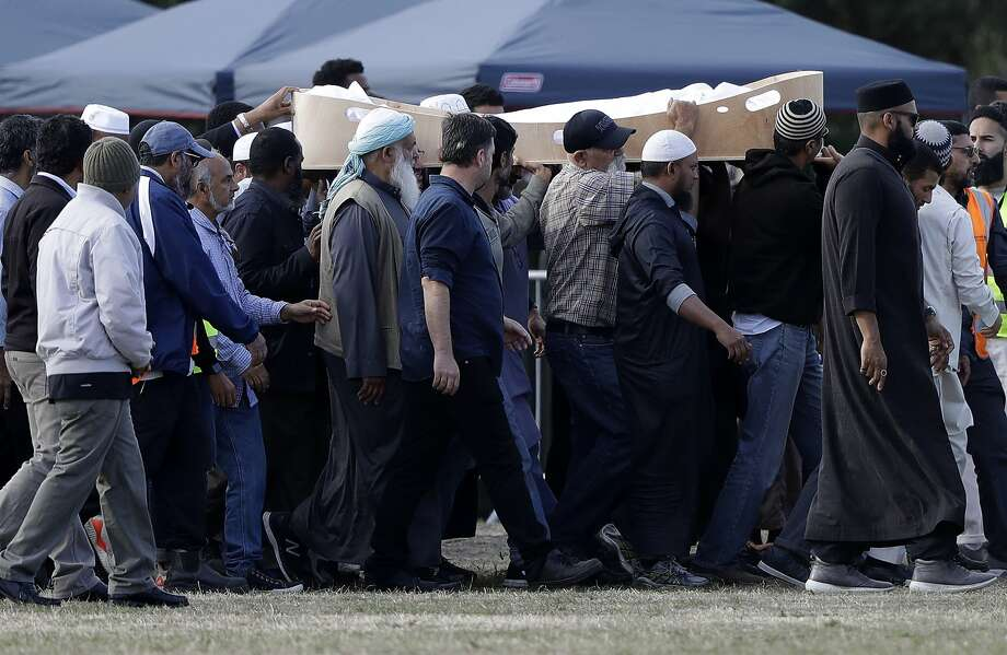 Mourners carry a victim of the shootings for burial at a Christchurch cemetery. Islamic tradition calls for bodies to be buried as soon as possible. Photo: Mark Baker / Associated Press