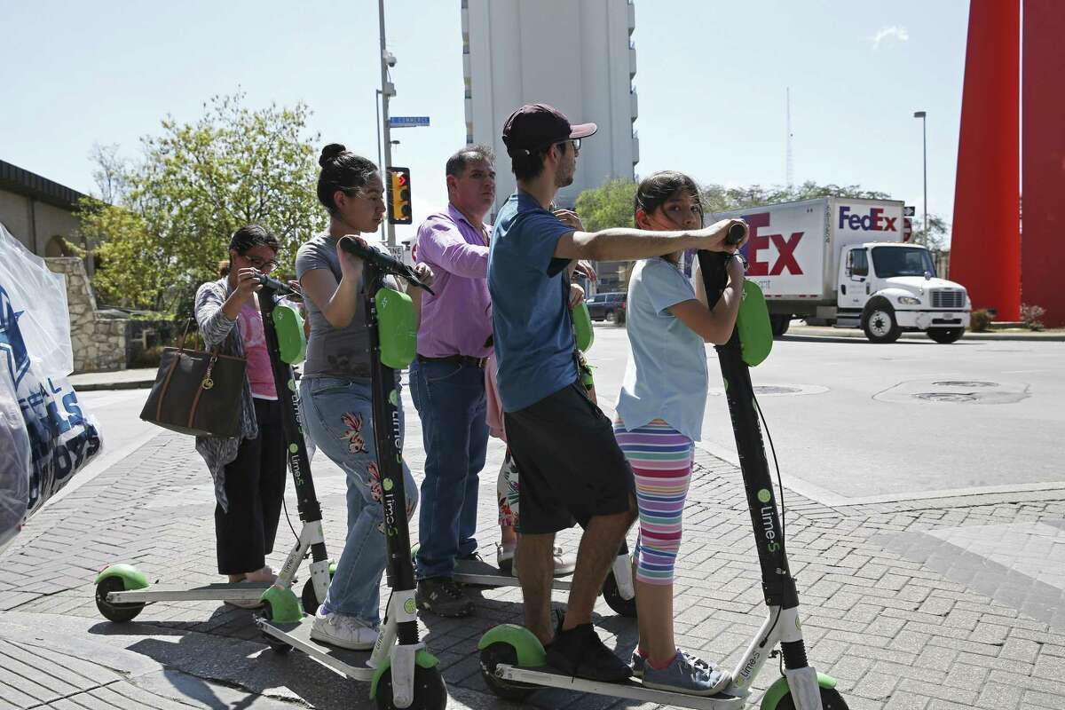 """A family, riding tandem, waits for a traffic light changes in downtown San Antonio, Wednesday, March 13, 2019. The scooter rental comes with an 18,404 agreement that straight jackets the customer. The riders had agreed to never sue Lime, take responsibility for all accidents and damage, accept binding arbitration in lieu of any jury trial, limit Lime's liability in any event to only $100, waive all participation in class action lawsuits and, among a maze of other promises, affirm that they've not had any drug or alcohol """"incidents"""" in the past seven years."""