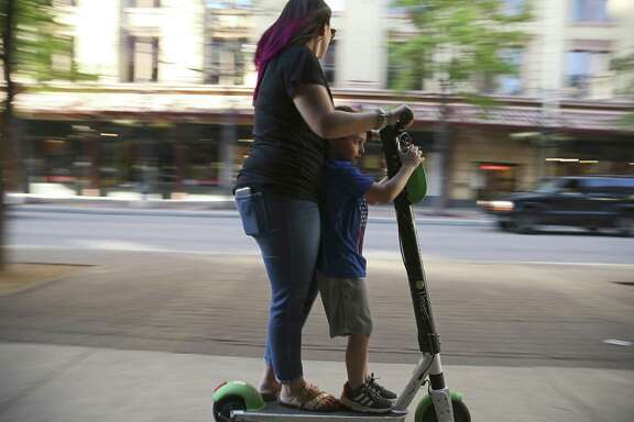 A woman uses a scooter in tandem on the sidewalk along Houston Street last month. The city is nearing key decisions on the future of the dockless vehicles in San Antonio, but requiring helmets seems off the table.
