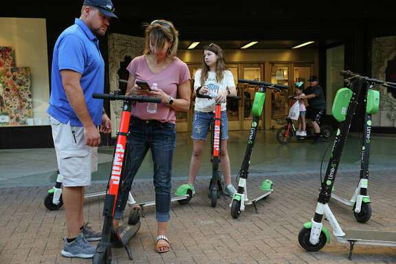 Clover Alexander, of Chico, uses her smartphone to rent scooters for her husband, Kevin Alexander and their daughter, Bethany, in downtown San Antonio last month. The City Council will soon discuss a proposal to reduce the number of scooter companies and vehicles allowed under a pilot program that has reached its end.