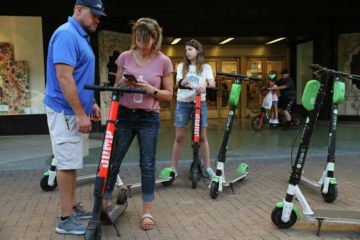 """Clover Alexander, of Chico, Texas, uses her smartphone to rent scooters for her husband, Kevin Alexander and their daughter, Bethany, in downtown San Antonio, Wednesday, March 13, 2019. The scooter rental comes with an 18,404 agreement that straightjackets the customer. The riders had agreed to never sue Lime, take responsibility for all accidents and damage, accept binding arbitration in lieu of any jury trial, limit Lime?•s liability in any event to only $100, waive all participation in class action lawsuits and, among a maze of other promises, affirm that they?•ve not had any drug or alcohol ?'incidents?"""" in the past seven years. They even agreed that Lime has never implied that its ?'equipment will be in good repair.?"""" Virtually every scooter company requires consent to a similar agreement before letting anyone activate one of the city?•s now-ubiquitous dockless vehicles."""