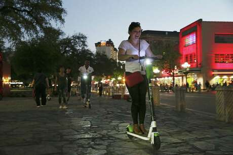 As the sun sets, scooters riders use the sidewalk of Alamo Plaza, Wednesday, March 13, 2019. The city will expand the areas it nominally doesn't allow the dockless vehicles to include parade routes and other Fiesta events.