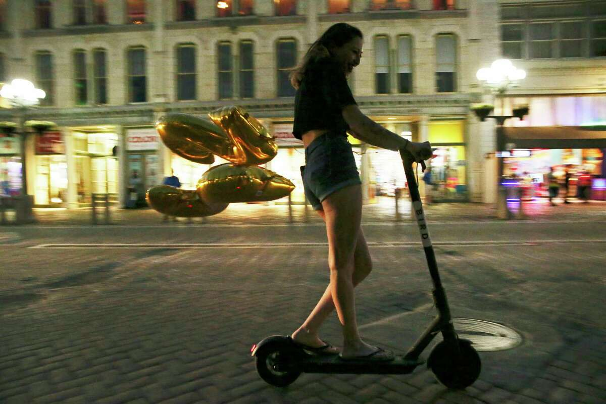A scooter zips by Alamo Plaza last March. The number of dockless vehicles has been steadily shrinking this year, and Lyft Scooters on Thursday announced it was pulling out, just one day after the city announced it was its top pick in a competition for a contract to operate here.