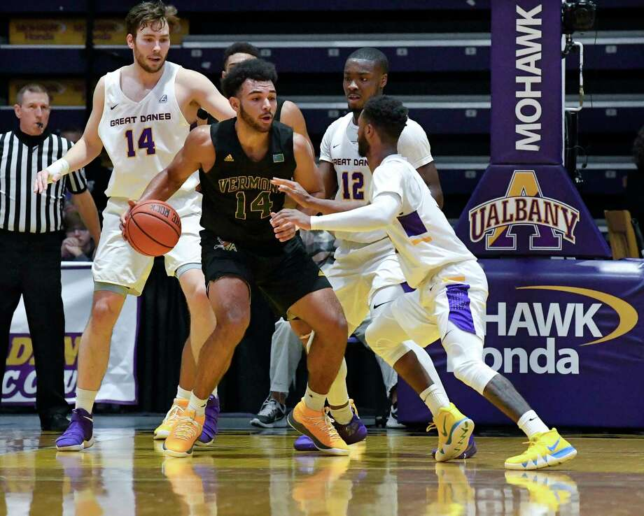 Vermont forward Isaiah Moll ,center, moves the ball against University at Albany defenders during the second half of an NCAA college basketball game Saturday, Jan. 5, 2019, in Albany, N.Y. Vermont won the game 80-51. (Hans Pennink / Special to the Times Union) Photo: Hans Pennink / Hans Pennink