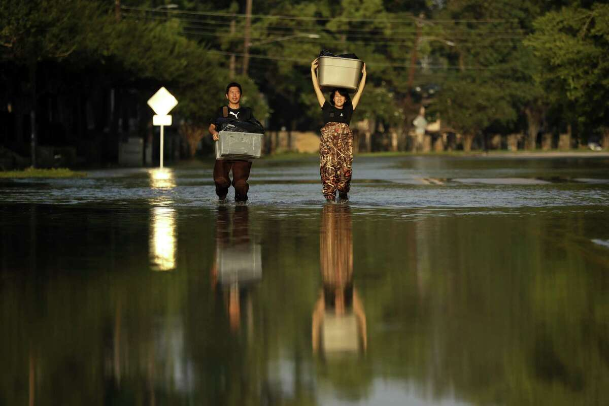 In this Monday, Sept. 4, 2017 file photo, Mariko Shimmi, right, helps carry items out of the home of Ken Tani in a neighborhood still flooded from Harvey in Houston. >>How Hurricane Harvey unfolded as told through social media