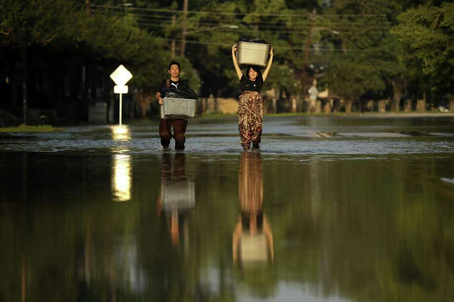 In this Monday, Sept. 4, 2017 file photo, Mariko Shimmi, right, helps carry items out of the home of Ken Tani in a neighborhood still flooded from Harvey in Houston. >>How Hurricane Harvey unfolded as told through social media Photo: Gregory Bull, STF / Associated Press / Copyright 2019 The Associated Press. All rights reserved.
